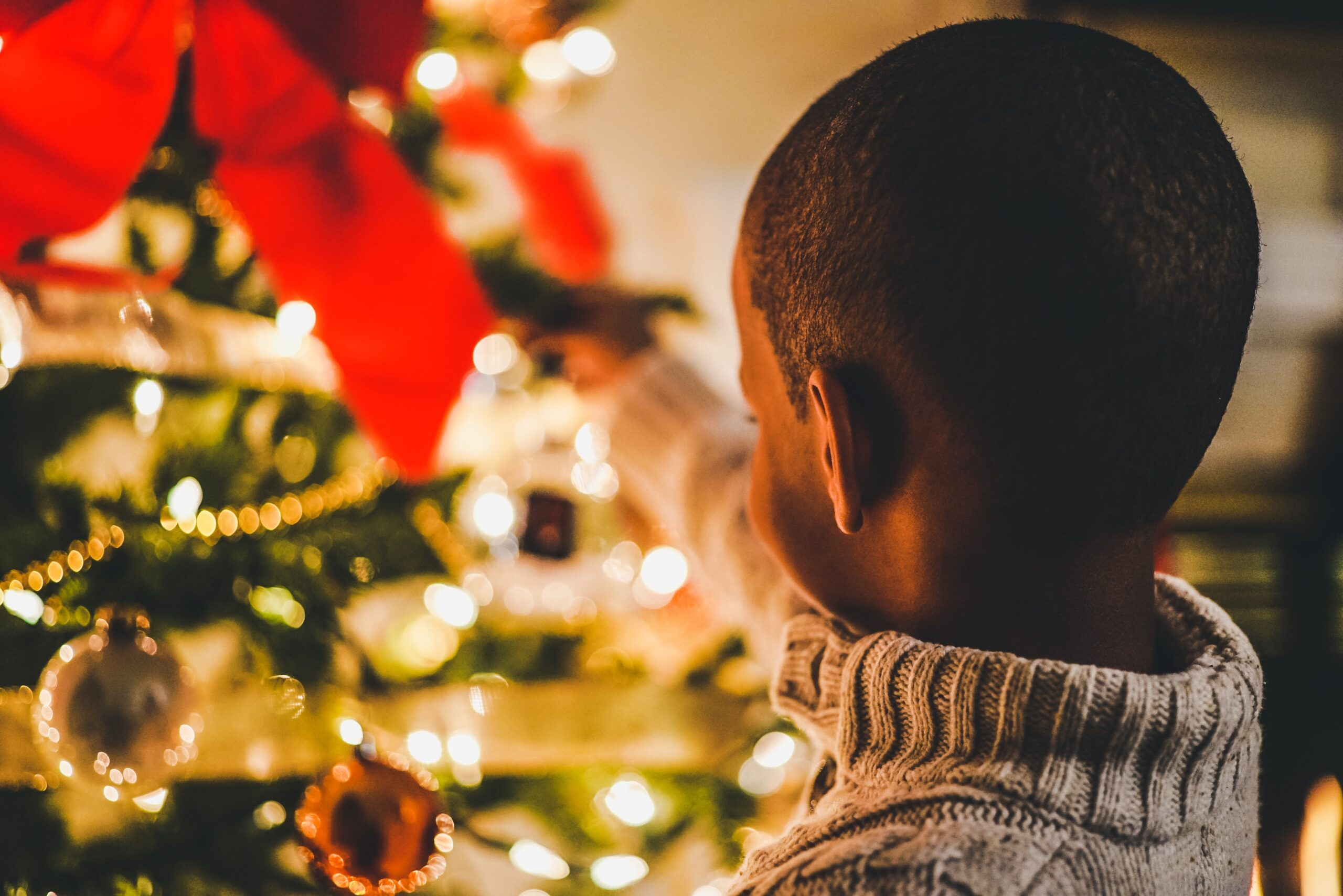 Child looking at a bright warm Christmas tree